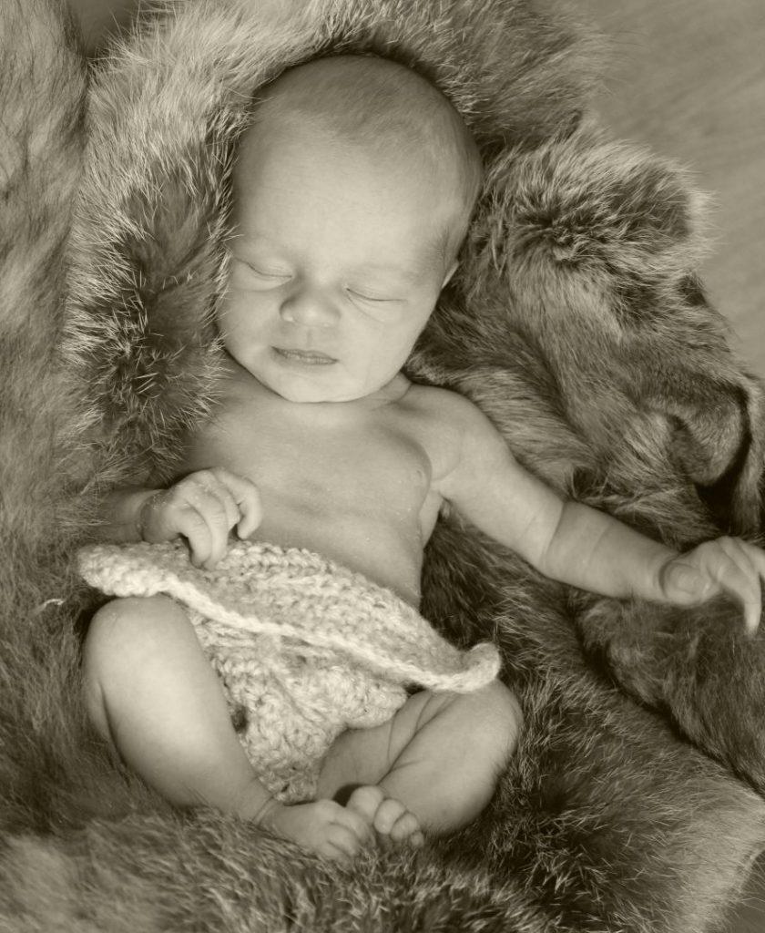 Ein besonders entzückendes Baby liegt (nur mit einer naturfarbenen, gehäkelten Windel bekleidet) in einem Fell