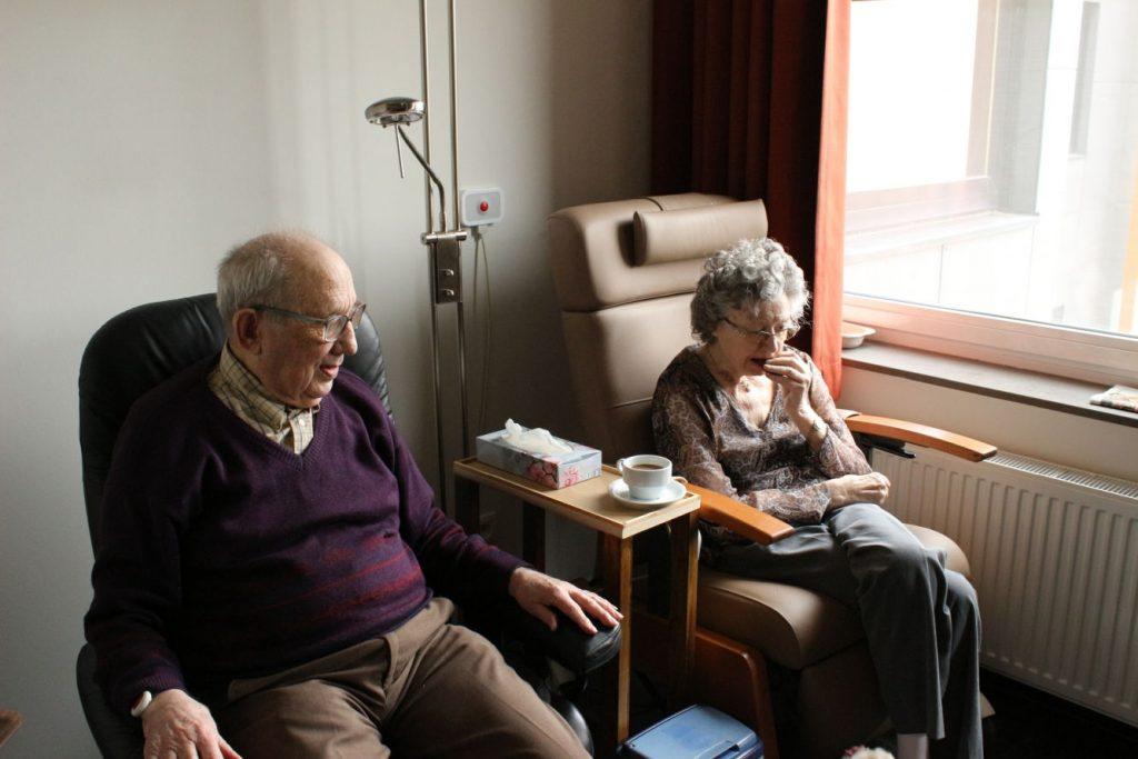 älteres Ehepaar sitzend im Wohnzimmer