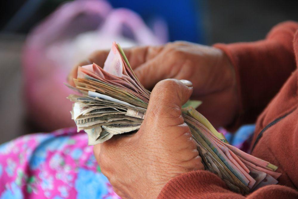 Eine alte Dame zählt Bargeld - viele, viele Scheine. Eine hohe Summe.Es ist nur ein Bildausschnitt zu sehen - rund um die Hände.