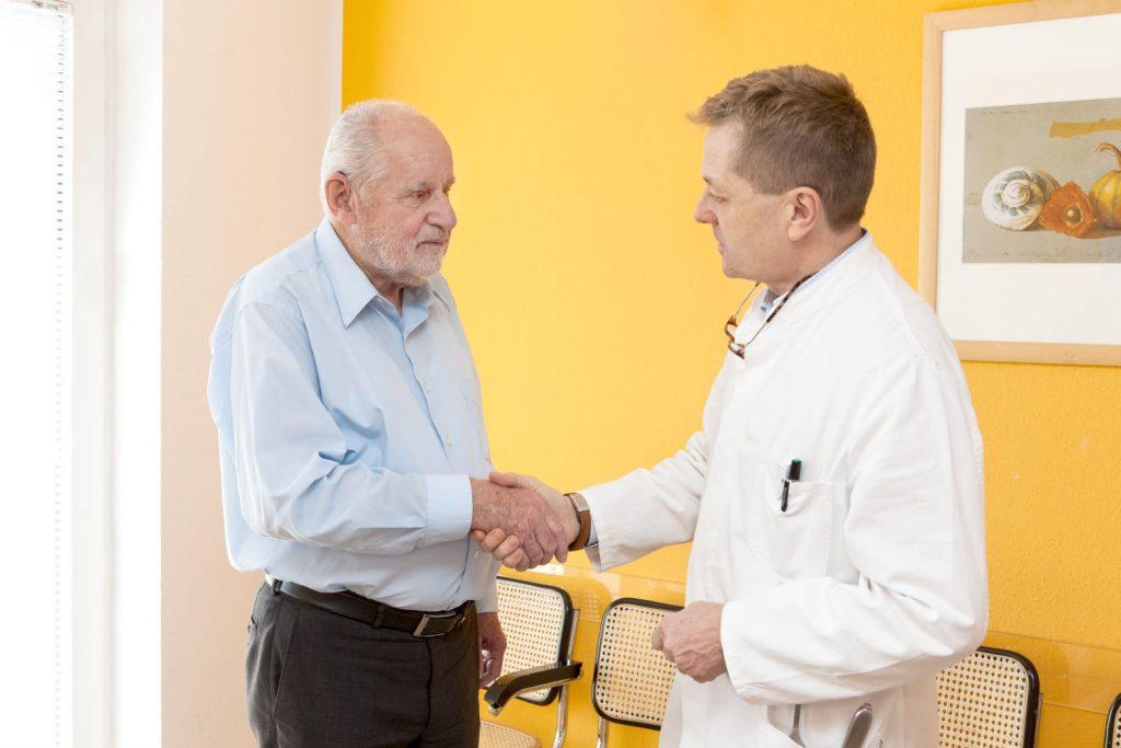 Arzt gibt Patienten die Hand
