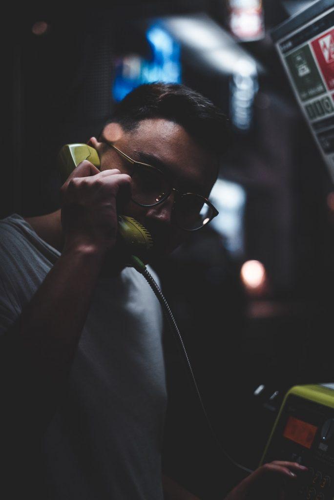 Mann an Telefonzelle