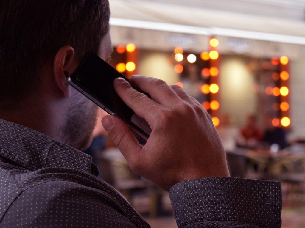 bärtiger Mann ruft vom Handy aus an.