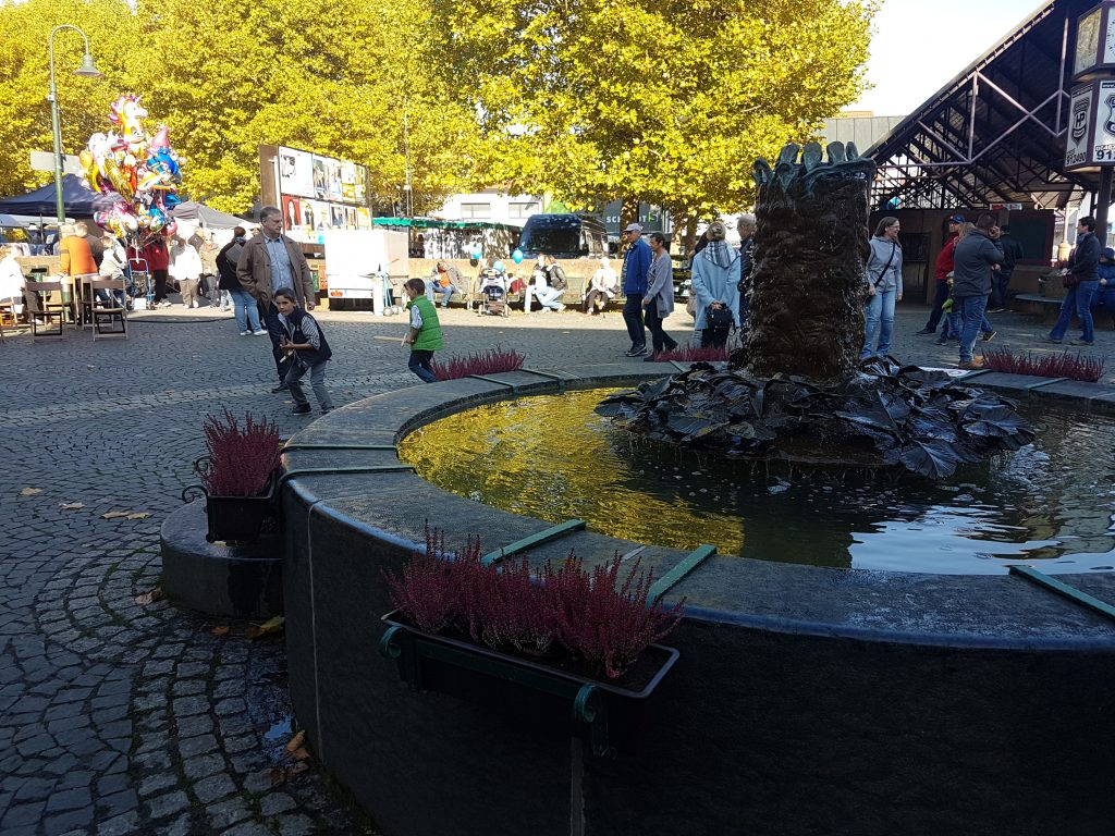 Marktplatz mit Brunnen und Leute drumherum.