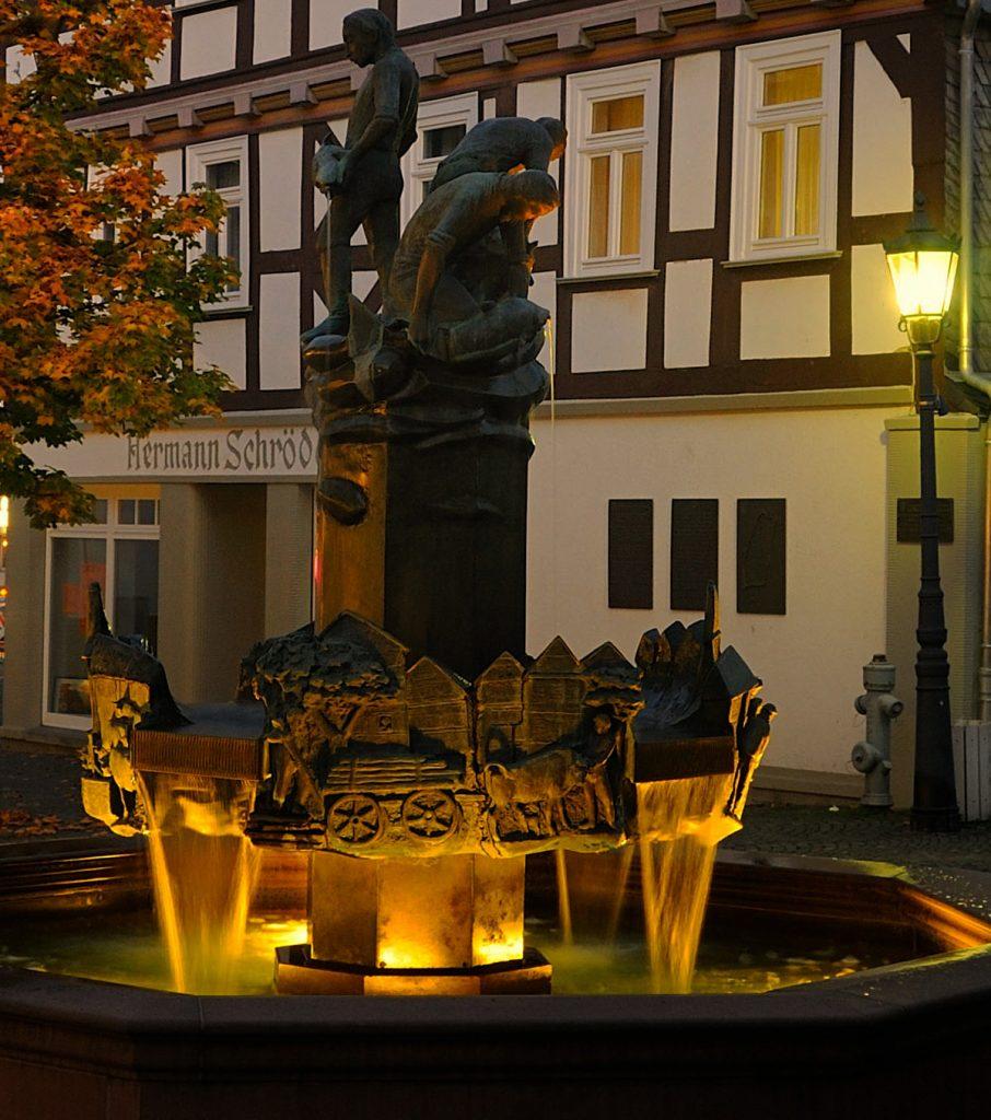 Ein Brunnen. Dahinter ein Fachwerkhaus. Der Brunnen hat einen bronzenen Wasserspeier mit Figuren obenauf und ist beleuchtet. Pferde und Wagen säumen den Kranz oberhalb. Es fließt Wasser.