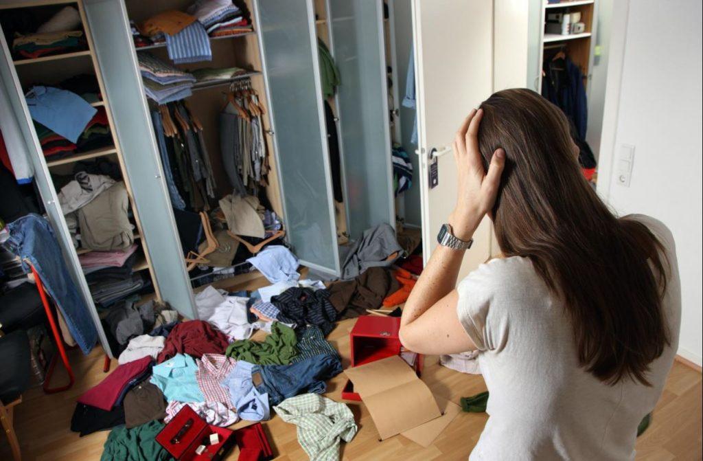 Frau steht entsetzt vor dem ausgeräumten Kleiderschrank. Die Sachen liegen zum Teil auf dem Boden. Ein Einbruch.