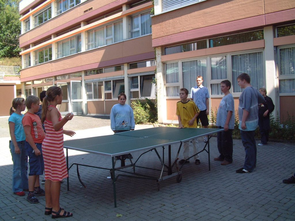 """Kinder vor der Schule stehen um die Tischtennisplatte. Sie spielen """"Rundlauf""""."""