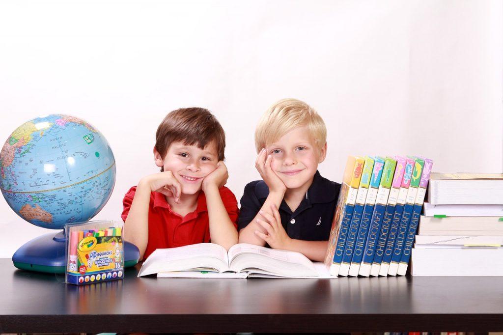 2 Schüler am Schreibtisch. Daneben Bücher und ein Globus