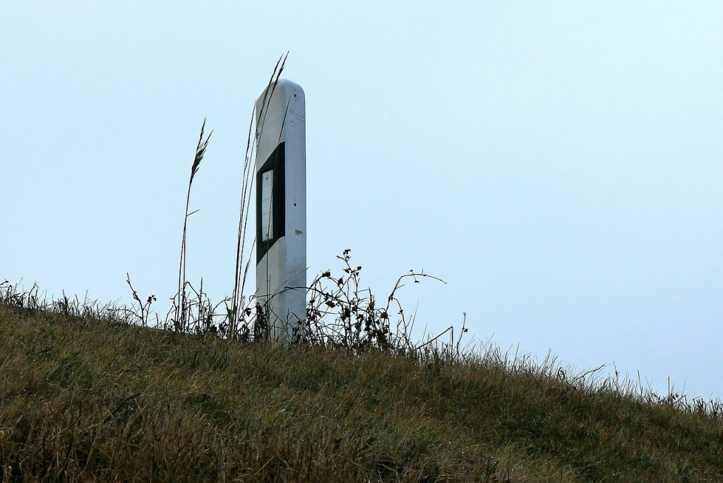 Ein Leitpfosten (unbeschädigt) steht am Straßenrand - der angrenzende Hang ist mit Gras bewachsen.