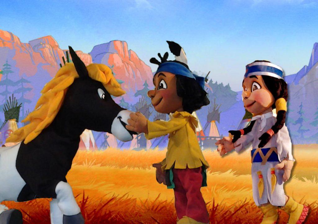 Yakari, seine Freundin und sein Pony vor gezeichneter Kulisse. Holzpuppen.