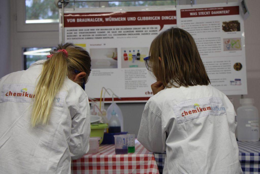 Zwei Mädchen stehen mit dem Rücken zur Kamera vor einem Tisch und schütten flüssige Substanzen zusammen.