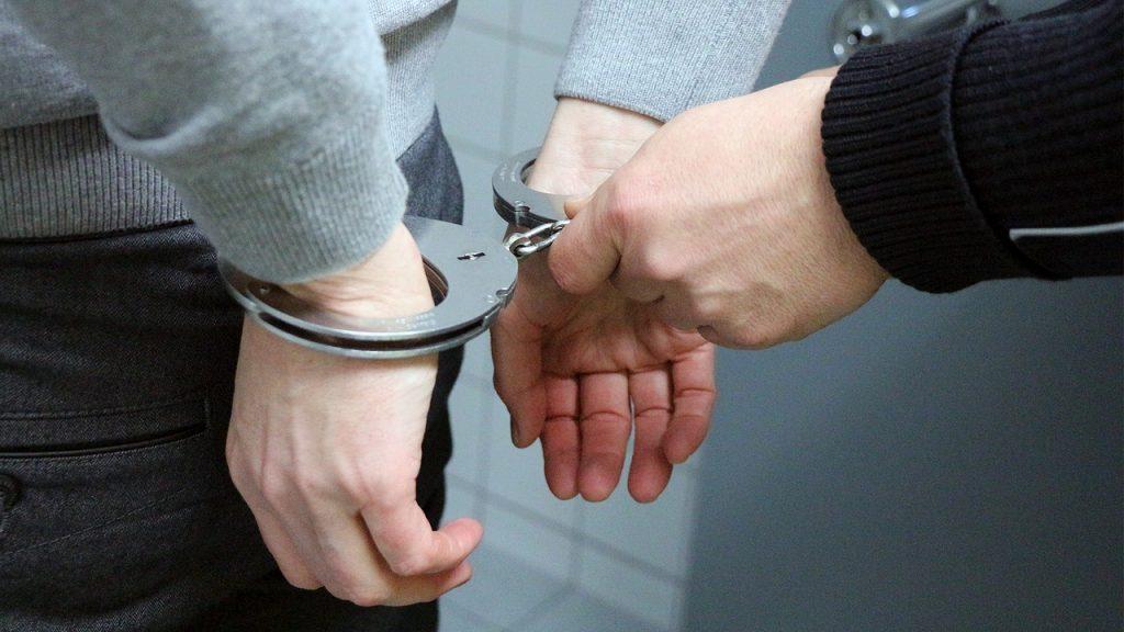 Mann mit Handschellen - es sind nur die Hände zu sehen die auf dem Rücken befindlich sind. Ein Polizeibeamter (Hände) befestigt die Handschellen.