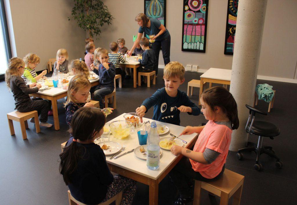 Ein Dutzend Kinder an kleinen Tischen beim Essen in der Kindertagesstätte. Keines hat sich am Gemüse bedient.