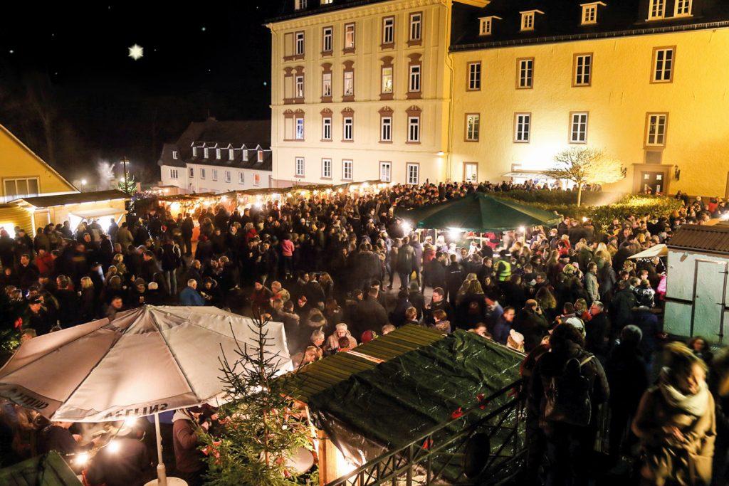 Das beleuchtete Schloss Wittgenstein und eine Menge von über 100 winterlich gekleideten Besuchern. Viele Buden sind auf dem Platz aufgebaut.