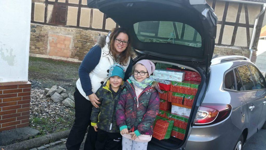 Frau mit 2 Kindern vor einem offenen Kofferraum mit Weihnachtspäckchen