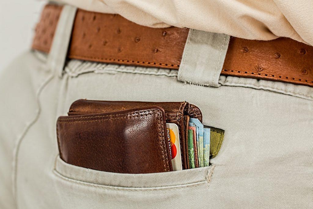 Eine rückwärtige Hosentasche eines Mannes aus der ein gut gefülltes Portemonnaie herausschaut.