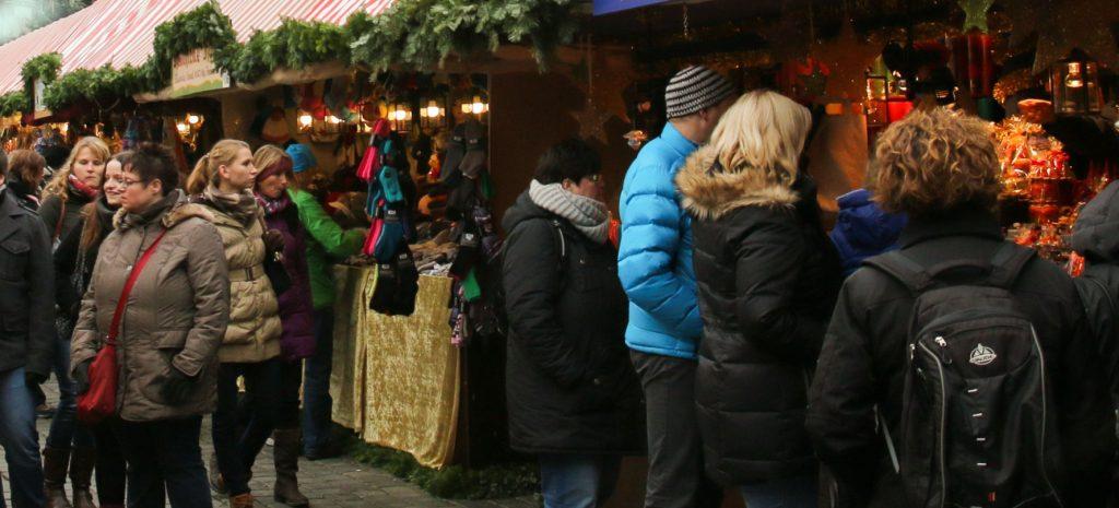Marktbuden, mit Tannengirlanden und Lichtern weihnachtlich geschmückt, Weihnachtsmarkt-Besucher schlendern entlang, schauen und kaufen.