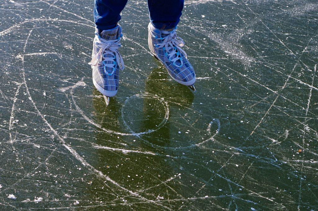 Ein Bildausschnitt: eine Eisfläche und zwei Kinderfüße in Schlittschuhen. Ein Stückchen von den Beinen ist zu sehen.