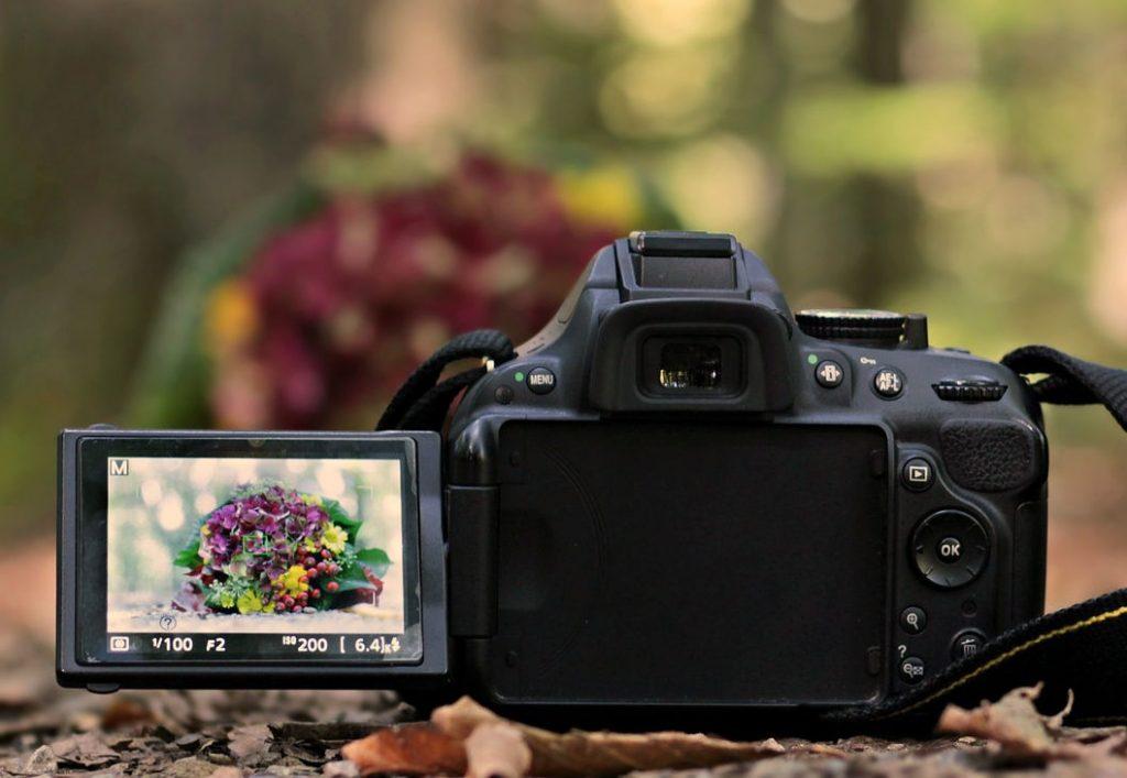 Kamera auf Stativ und im Sucher ein Blumenbouquet