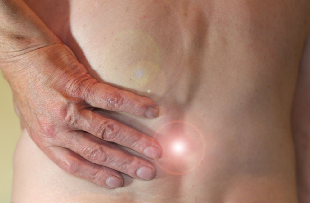 """Ein nackter Rücken. Ein Mann reibt sich diesen. Ein """"Schmerzpunkt"""" ist angezeichnet."""