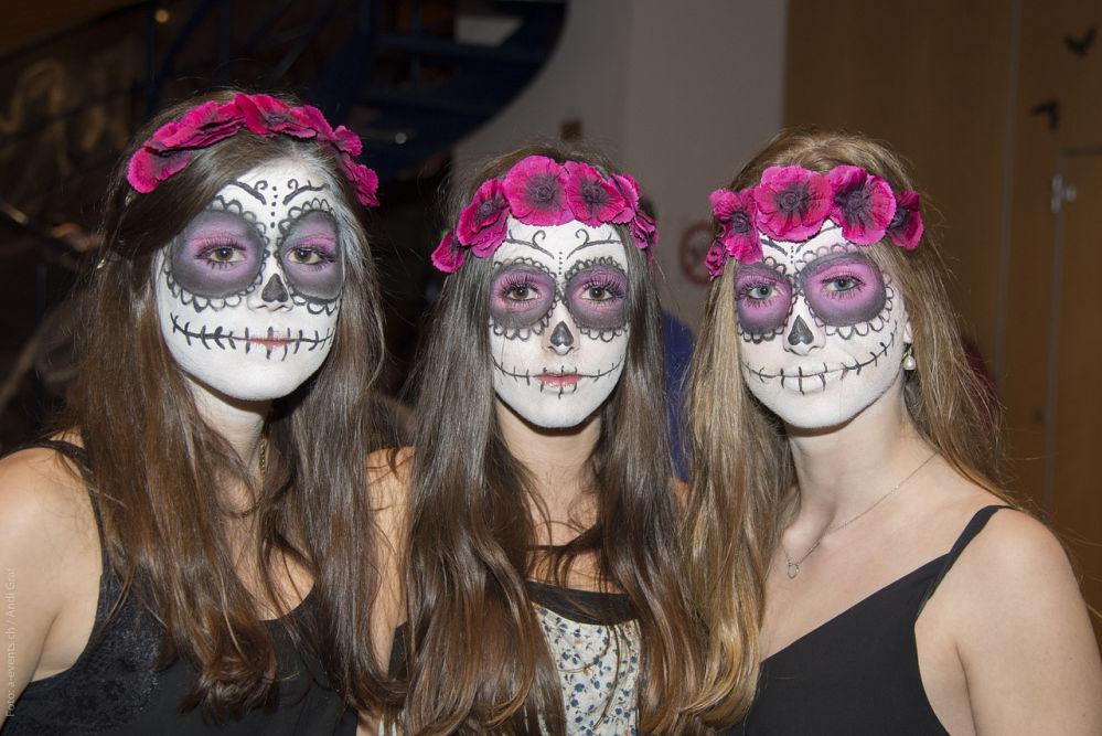 Drei maskenhaft geschminkte und blumenbekränzte Mädchen