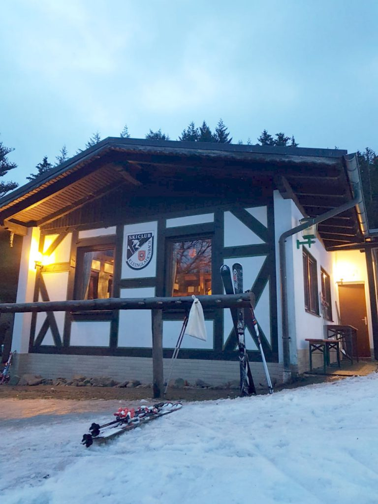 Skihütte. Fachwerkfront. Beleuchtet. Ski davor angelehnt. Es hat geschneit. Das Wappen des Skiclubs Kleingladenbach ziert die Vorderseite.