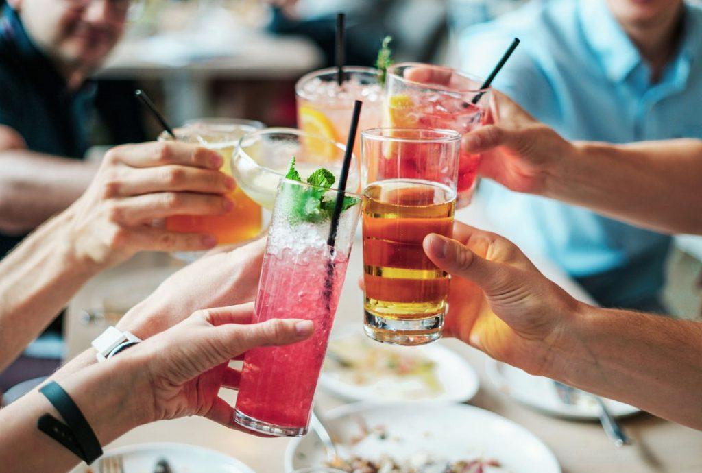 Junge Leute stoßen mit Getränken an
