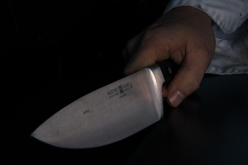 Eine Hand, die ein großes, metallenes Messer hält. Bedrohliche Geste.