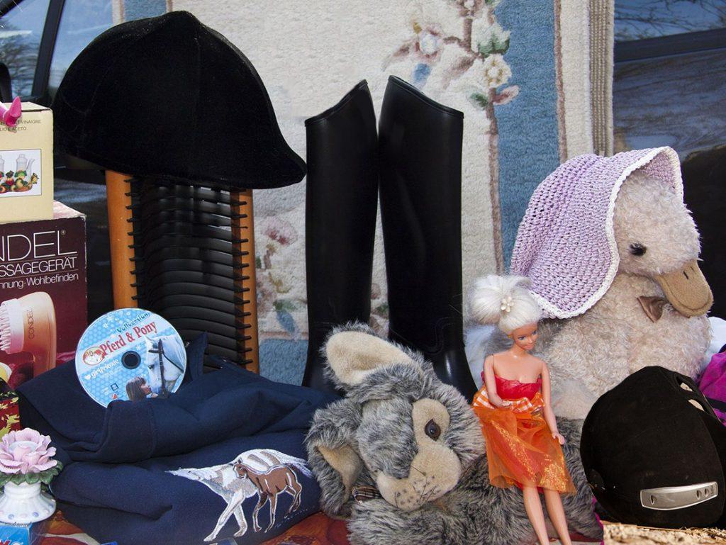 Kinderspielsachen, Barbie, Plüschtier, CD... auf einem Flohmarkttisch.