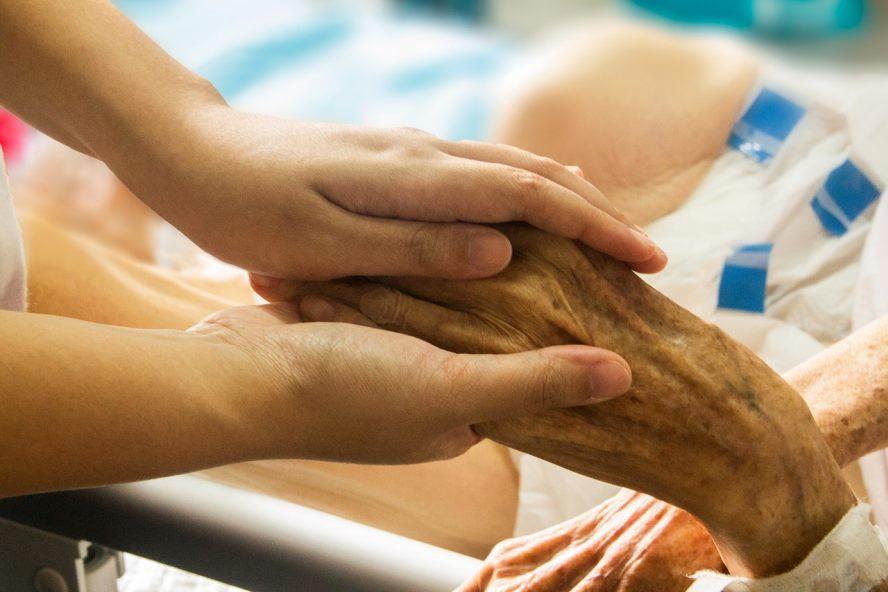 Junge Person hält faltige Hand einer Patientin.