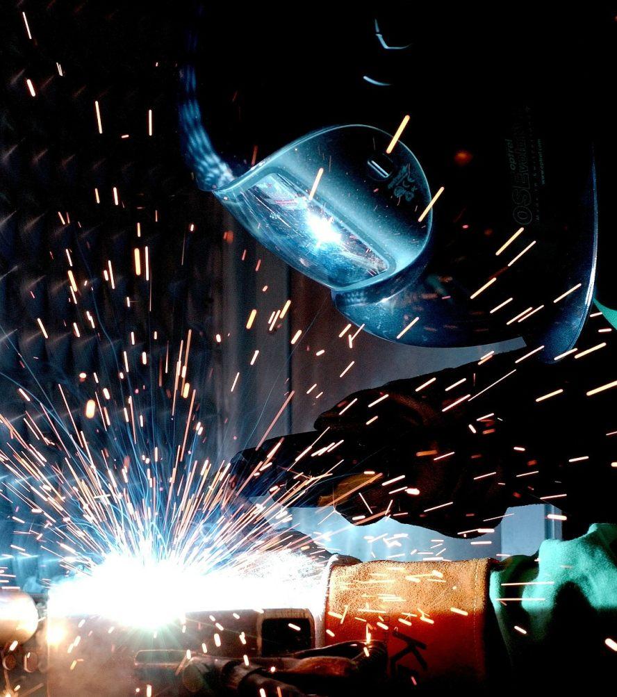 Ein Schweißer in Schutzausrüstung schweißt ein Arbeitsstück