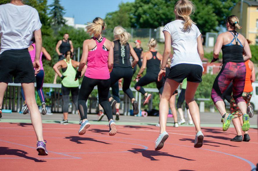 Hüpfende Frauen in einer Gruppe in Sportkleidung auf einem Sportplatz im Freien.