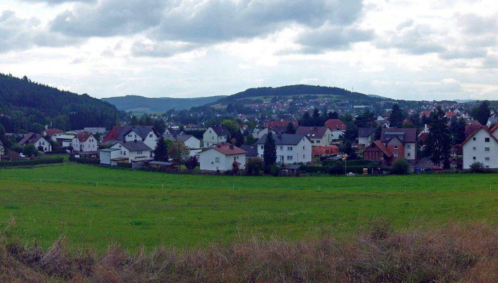 Gladenbach - Häuser von Nordosten aus. Vorn: Wiese. Hinten: Berge und Himmel.