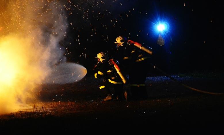 Feuerwehr löscht im Freien einen Brand