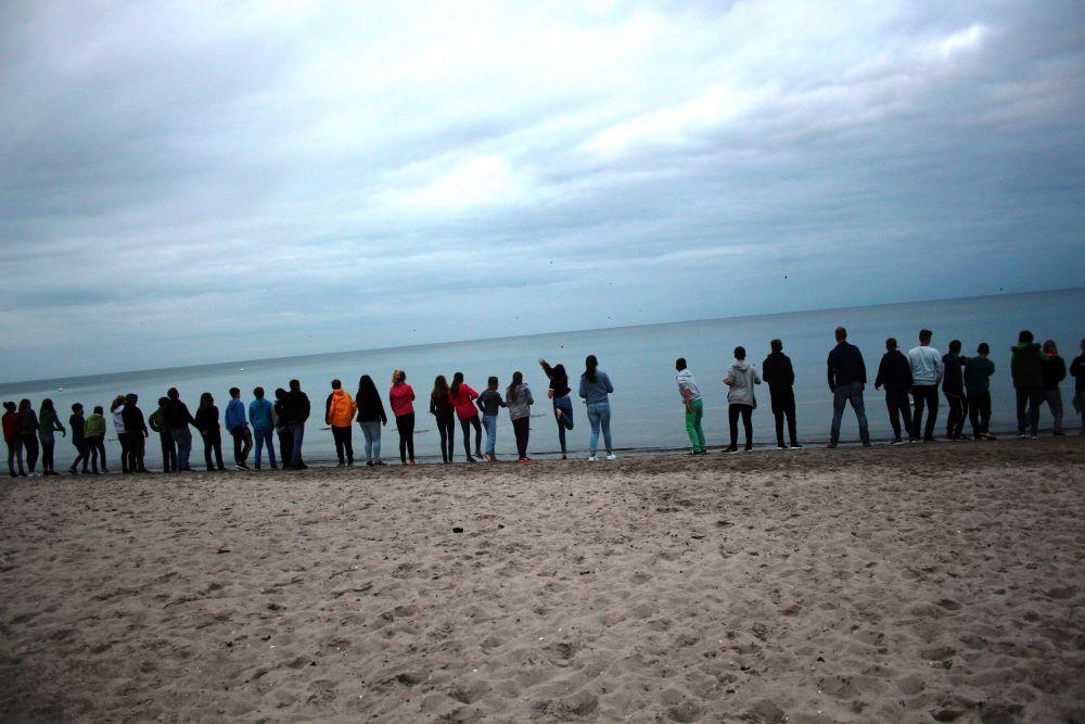 Etwa drei Dutzend Jugendliche stehen bei Dämmerung am Meeresstrand in einer Reihe.