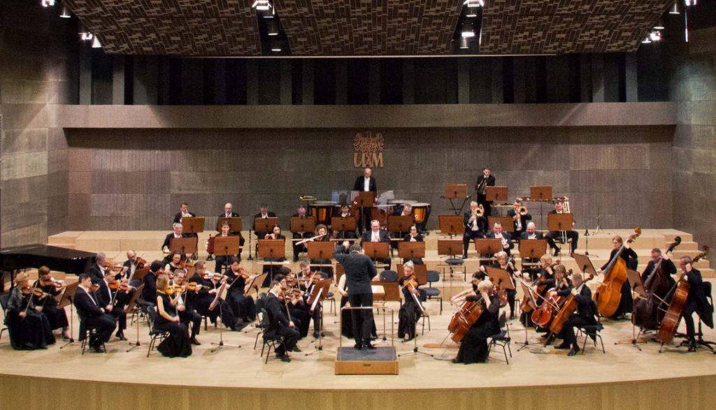 Ein großes Orchester in einem Konzertsaal. Alle Musiker festlich gekleidet und mit ihren Instrumenten spielend.