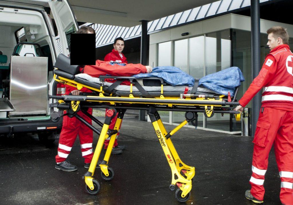 Verletzer auf Trage und Sanitäter vor Klinikum