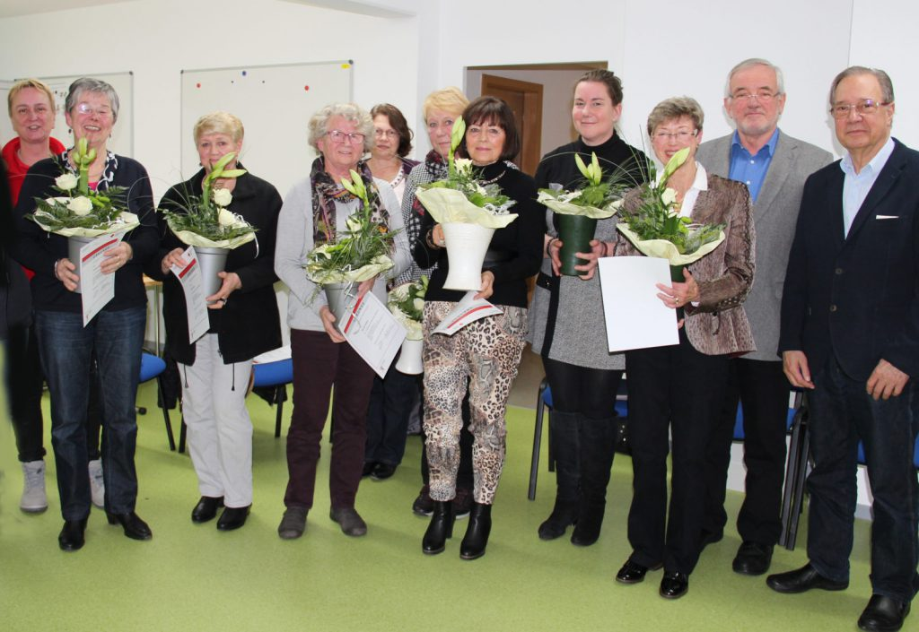 """Die geehrten Übungsleiterinnen mit Blumensträußen und die """"Offiziellen"""" mit beim Gruppenfoto."""