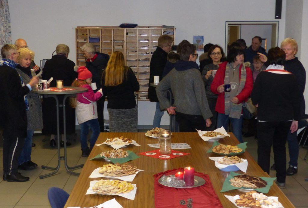 Vor gedecktem Tisch mit Plätzchen und Kerzen stehen die Besucher der Veranstaltung und unterhalten sich angeregt, die Teetassen in der Hand.