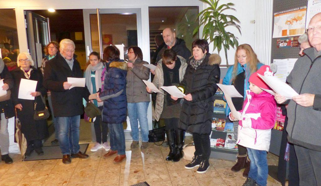Eine Gruppe von winterlich gekleideten MEnschen aller Altersgruppen stehen - Liedblätter haltend - im Foyer des FeG-Gemeindehauses in Biedenkopf und singen.erner)