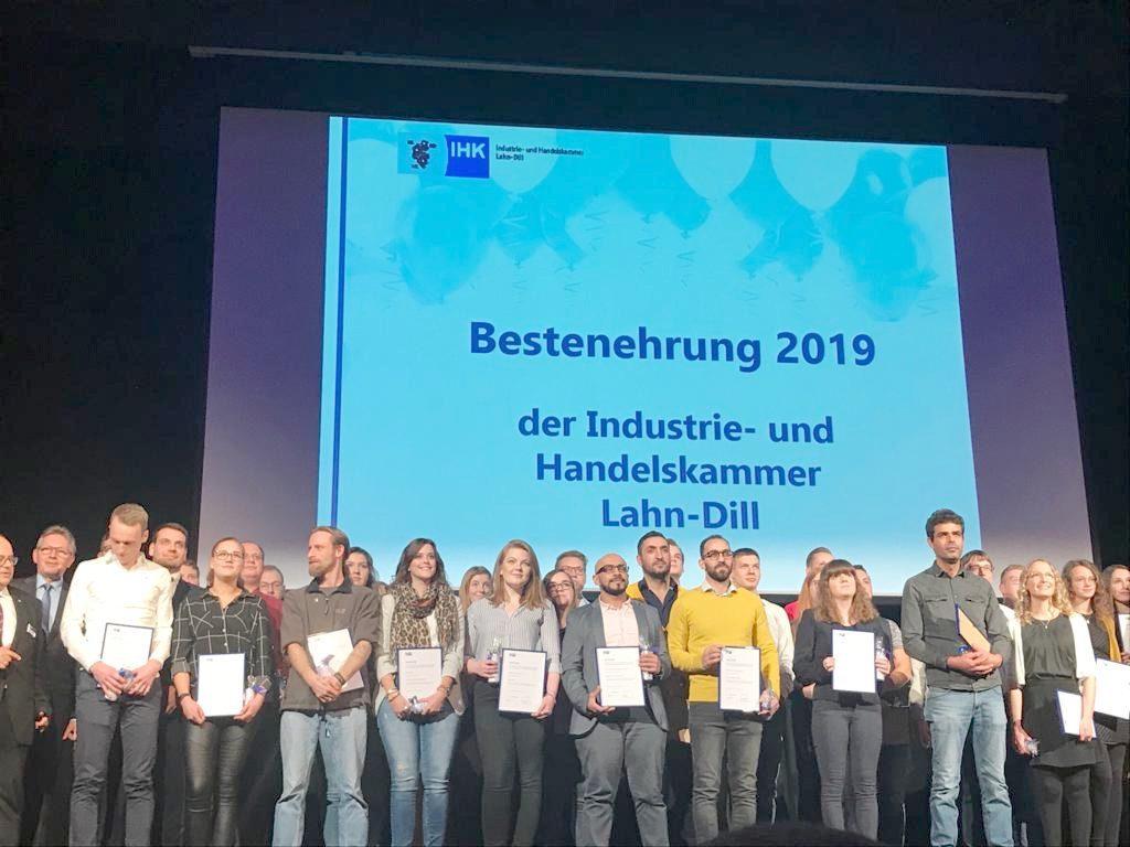 """Vor der Beamer-Leinwand mit dem Titel """"Bestenehrung 2019"""" haben sich die erfolgreichen Absolventen mit ihren Urkunden zum Gruppenfoto aufgestellt."""