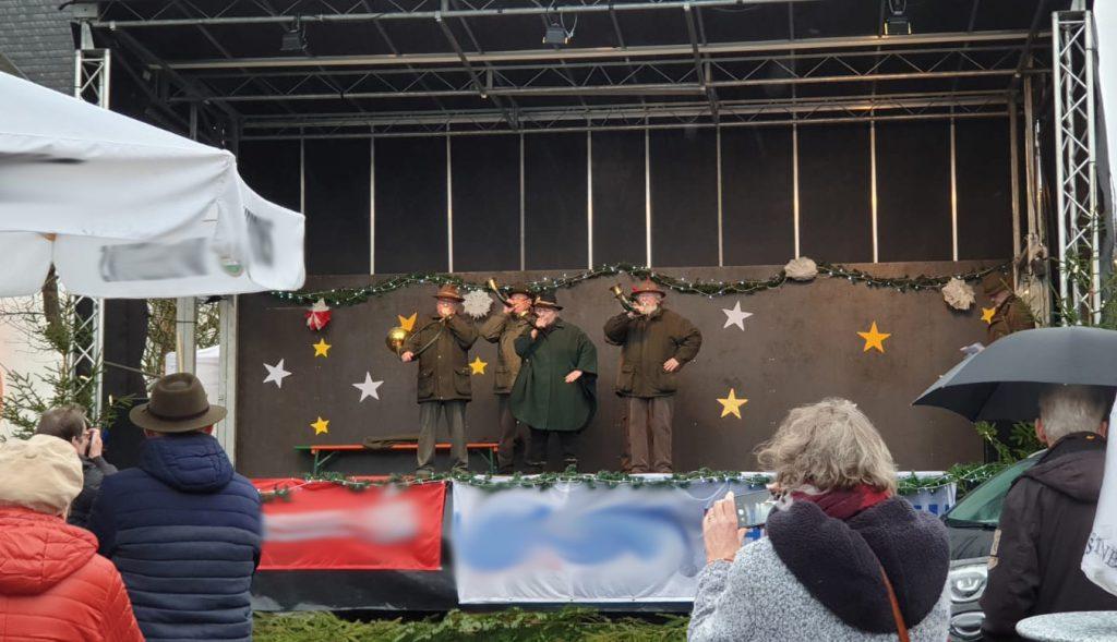 Vier Jagdhornbläser stehen auf der sternengeschmückten Aktionsbühne und musizieren. Davor einige Besucher.