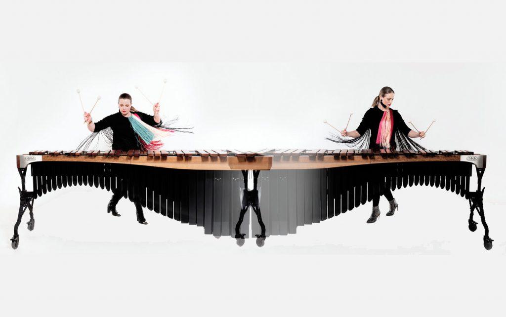 Zwei junge Frauen, präsentieren an einem großen Xylophon gleichzeitig ihre musikalischen Fertigkeiten.