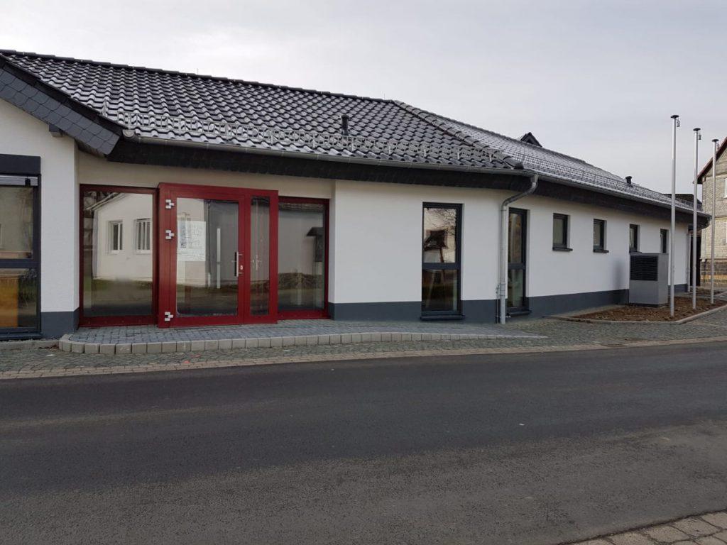 Der neue Dorftreff in Herzhausen. Rote Eingangstür. Flach geneigtes Dach, moderne Architektur.