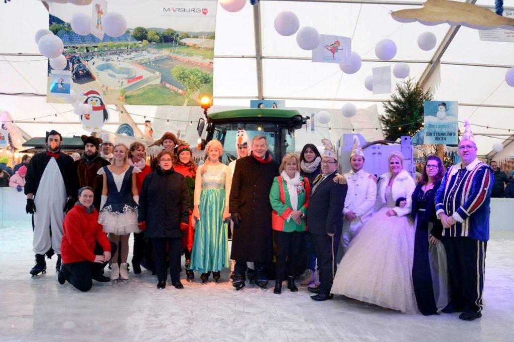 Bürgermeister Spies und verkleidete Eisläufer (Pinguin, Prinzessin, Prinz, Balletttänzerin...) stehen auf dem Eis im Eispalast Marburg.
