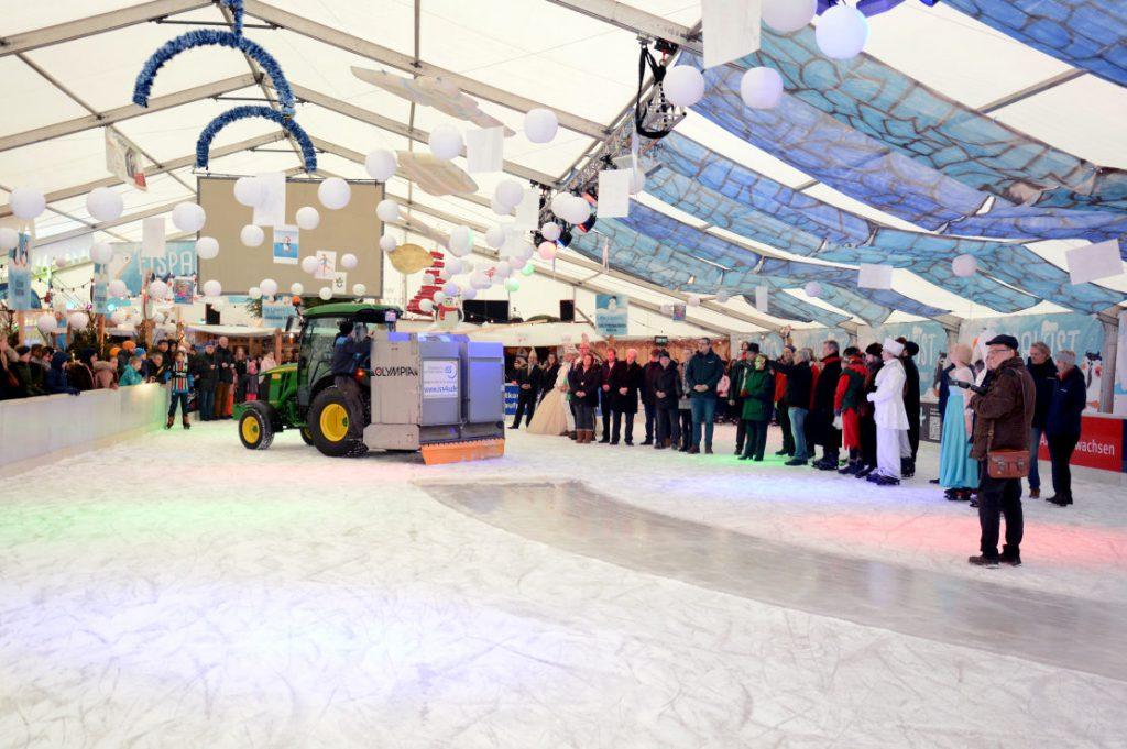 Ehrengäste stehen auf dem Eis und bewundern in der Mitte die neue Eismaschine.