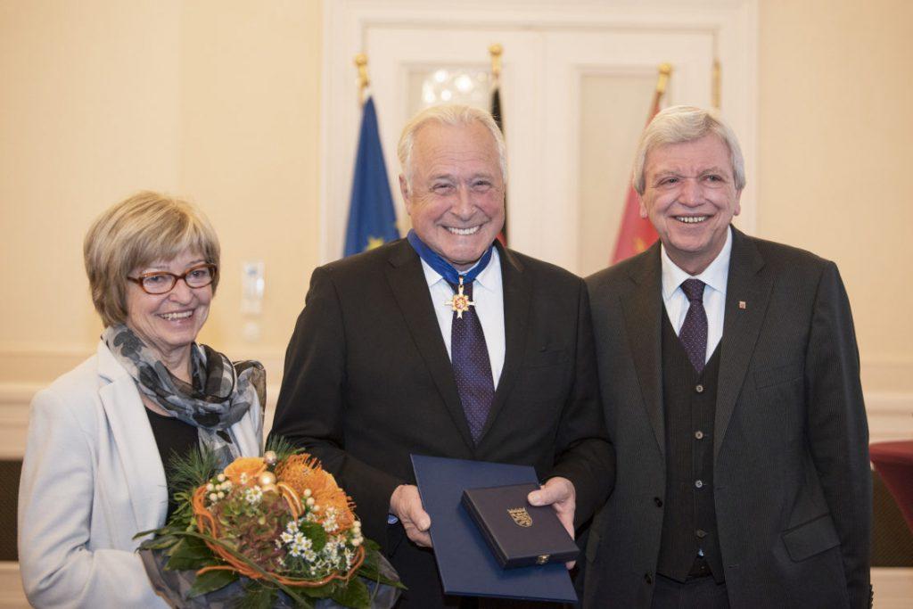 Frau Fischbach mit Blumenstrauß, Robert Fischbach in der Mitte mit dem neuen Verdienstorden um den Hals und rechts Minister Bouffier. Alle strahlen.
