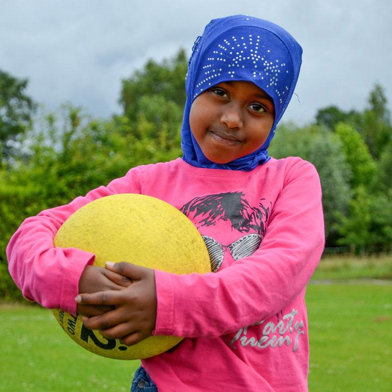 Flüchtlingskind. Schwarz. Mit Kopftuch. Etwa sieben Jahre alt. Steht auf einer Wiese und hält einen gelben Ball im Arm.