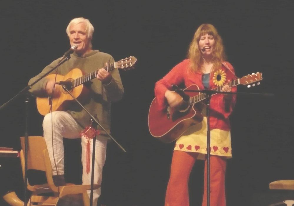 Ein Mann und eine Frau - beide mit Gitarre im Anschlag - singen vor schwarzem Hintergrund.