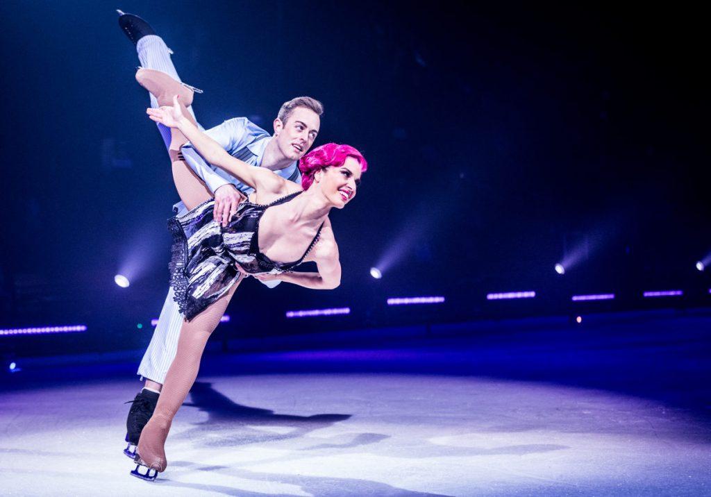 Ein Eislaufpaar in tänzerischer Pose auf beleuchteter Eisfläche.