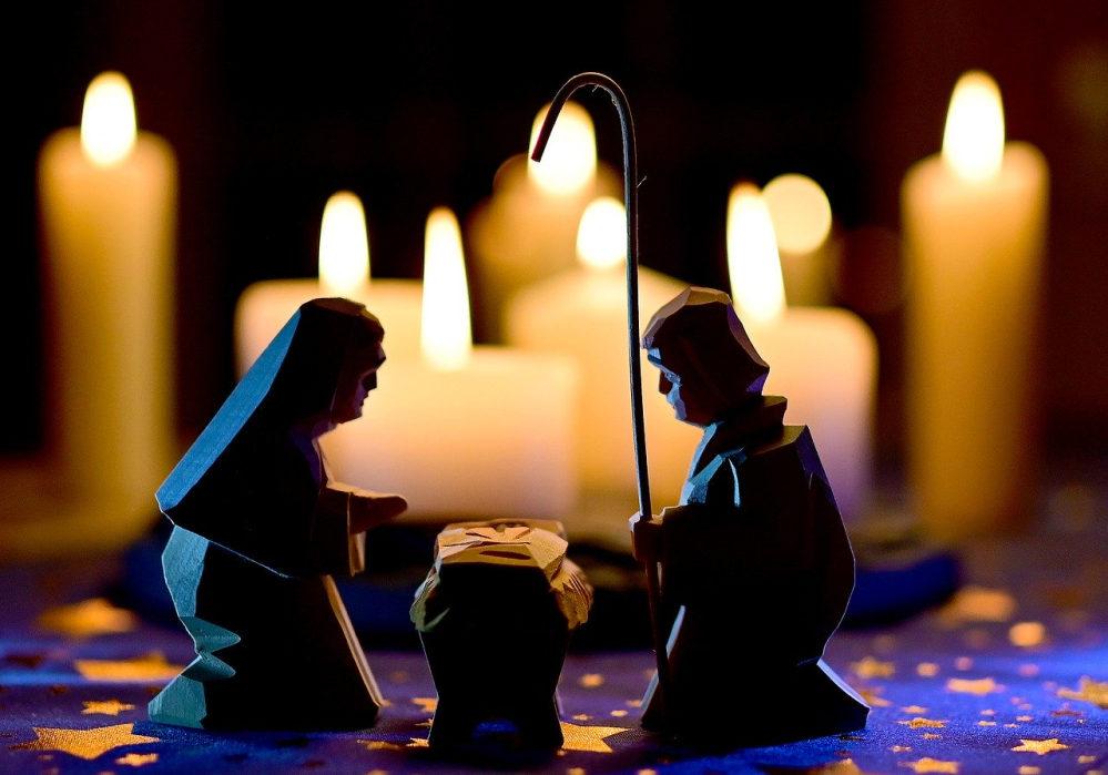 Brennende Kerzen im Hintergrund. Vorn - geschnitzt - die Heilige Familie mit dem Jesuskind in der Krippe.